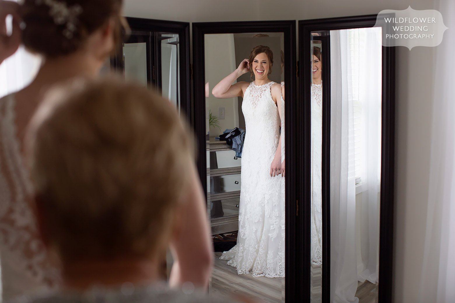 Bride looks at herself in mirror at Cooper's Ridge in Boonville, MO.