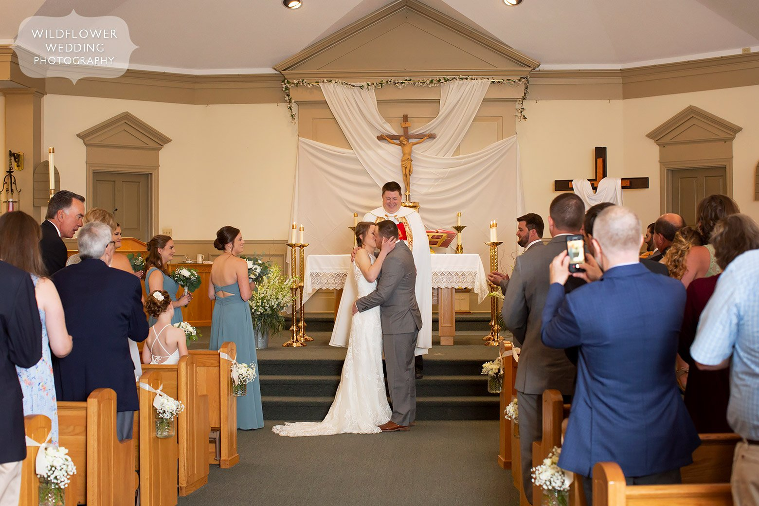 Bride and groom kiss at end of church ceremony in Boonville, MO.