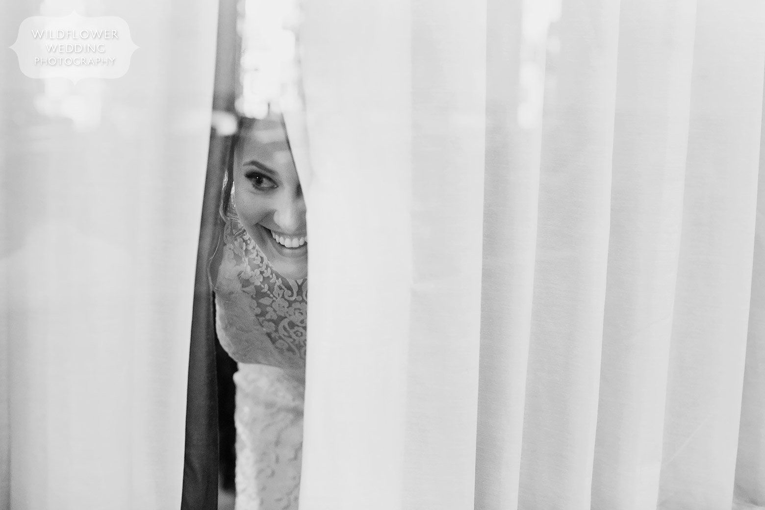 Candid wedding photography of bride looking out of curtains at guests.