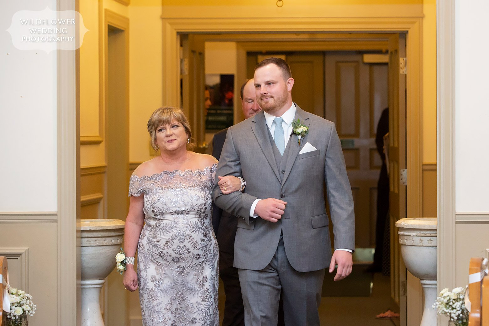 Groom walks down aisle with parents in Boonville, MO.