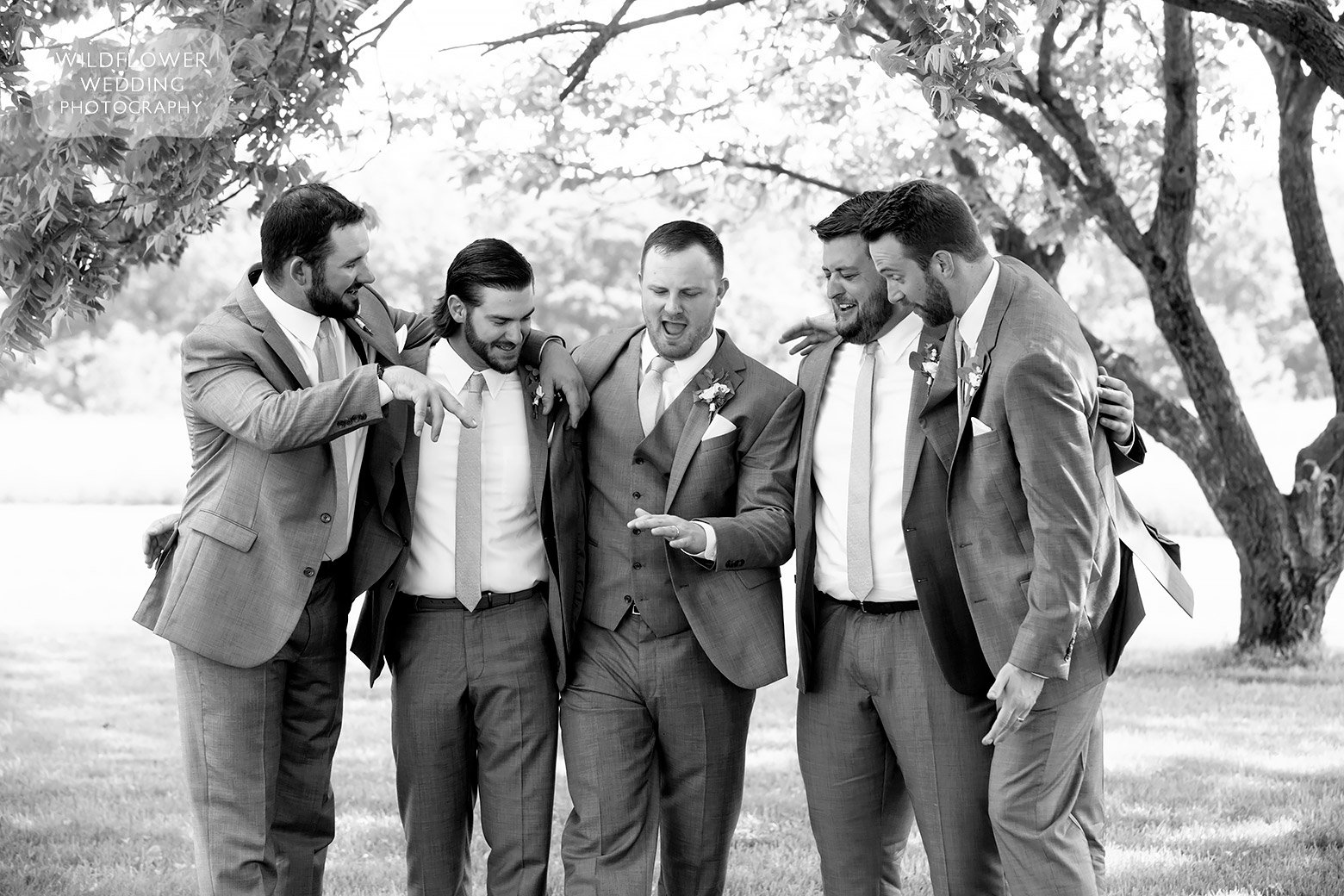 Groom checks out ring with groomsmen in Boonville, MO.
