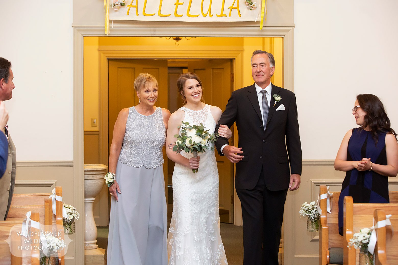 Bride enters ceremony with her parents in Boonville, MO.