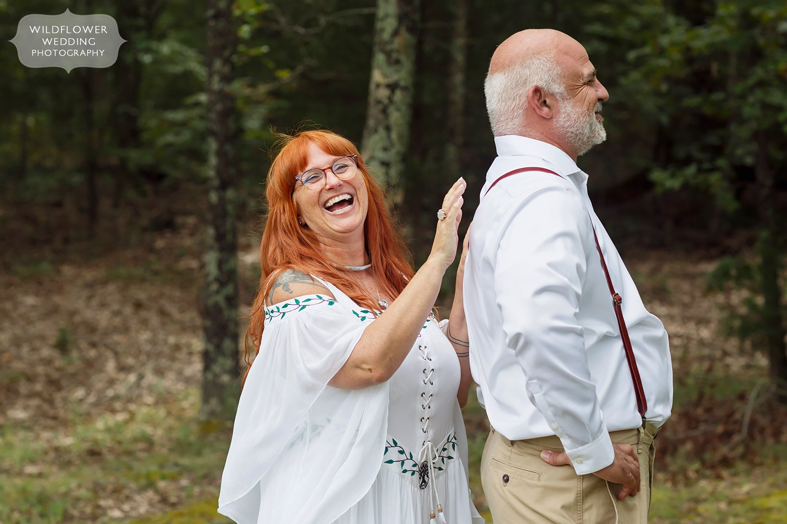 Bride taps groom on back before their first look in southern Missouri.
