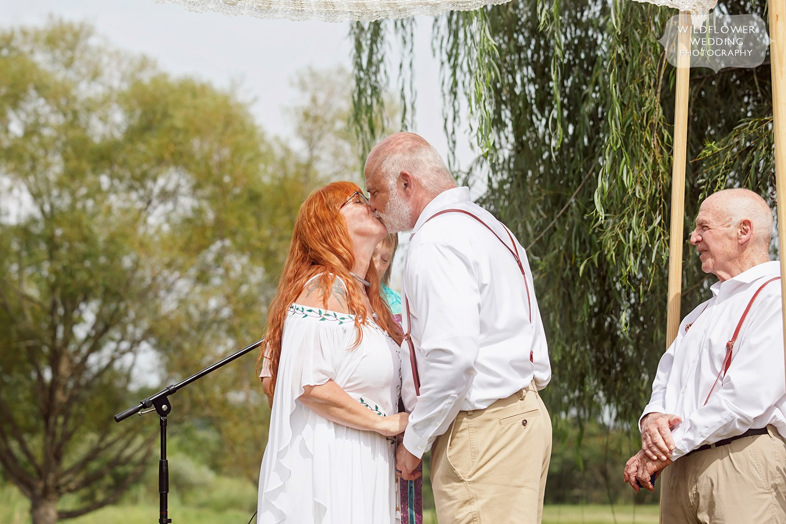 The bride and groom kiss during their outdoor ceremony in southern MO.