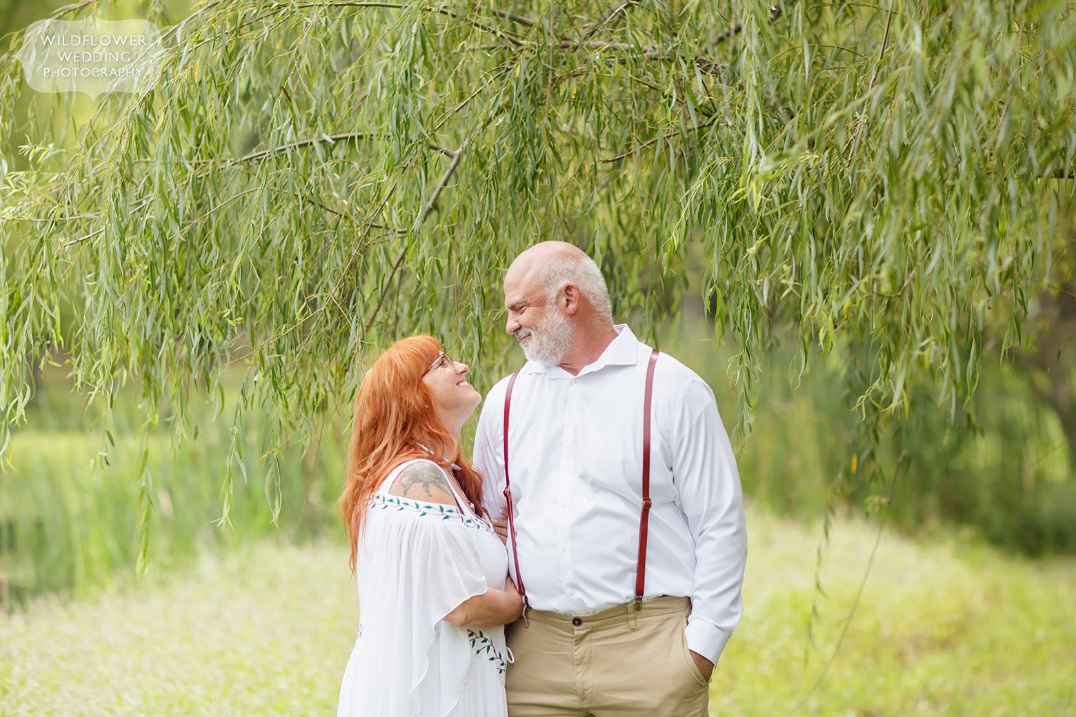 Bride and groom look at each other under a weeping willow in Missouri.