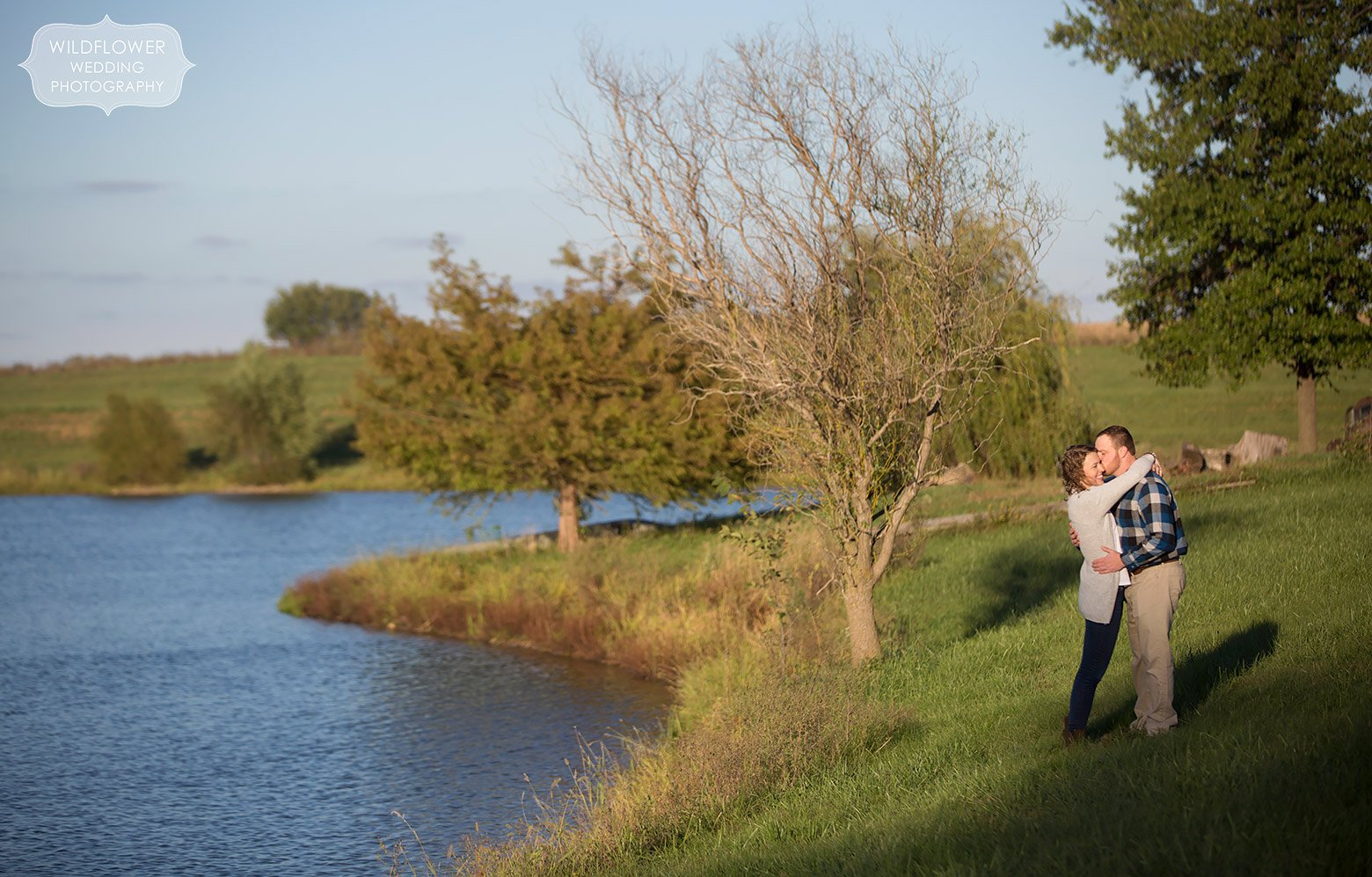 Couple stands by a pond during their country engagement session at a family farm Boonville, MO.