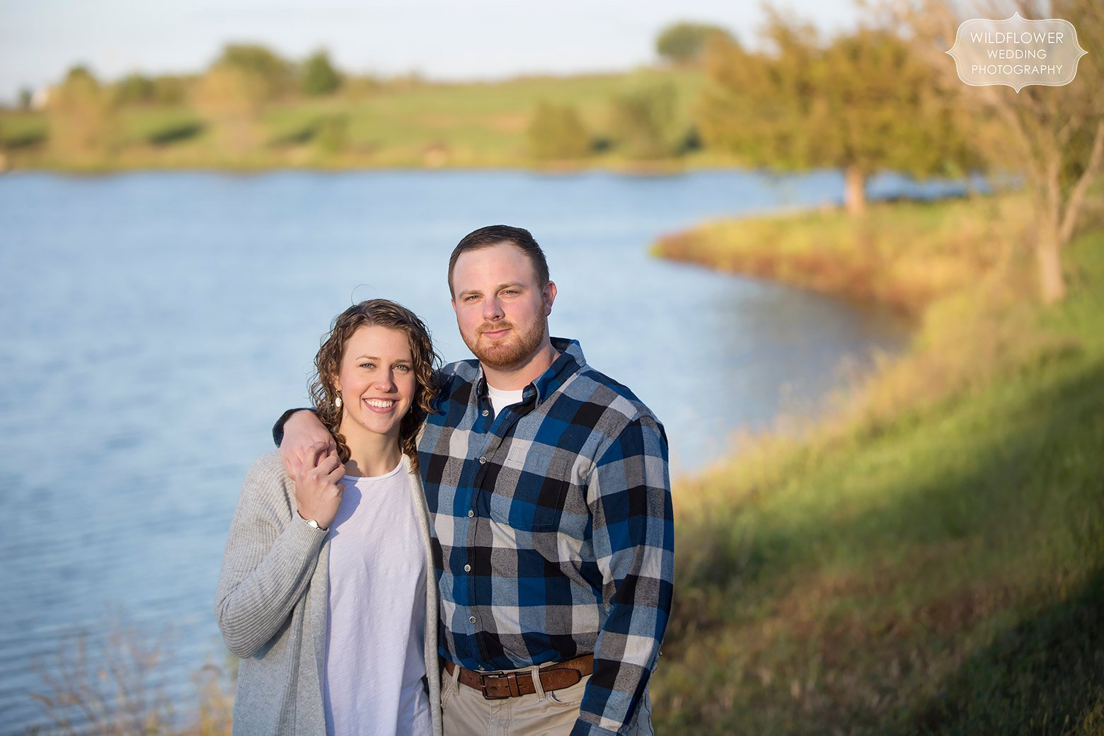 Couple stands next to a pond during their country engagement session at their family farm.