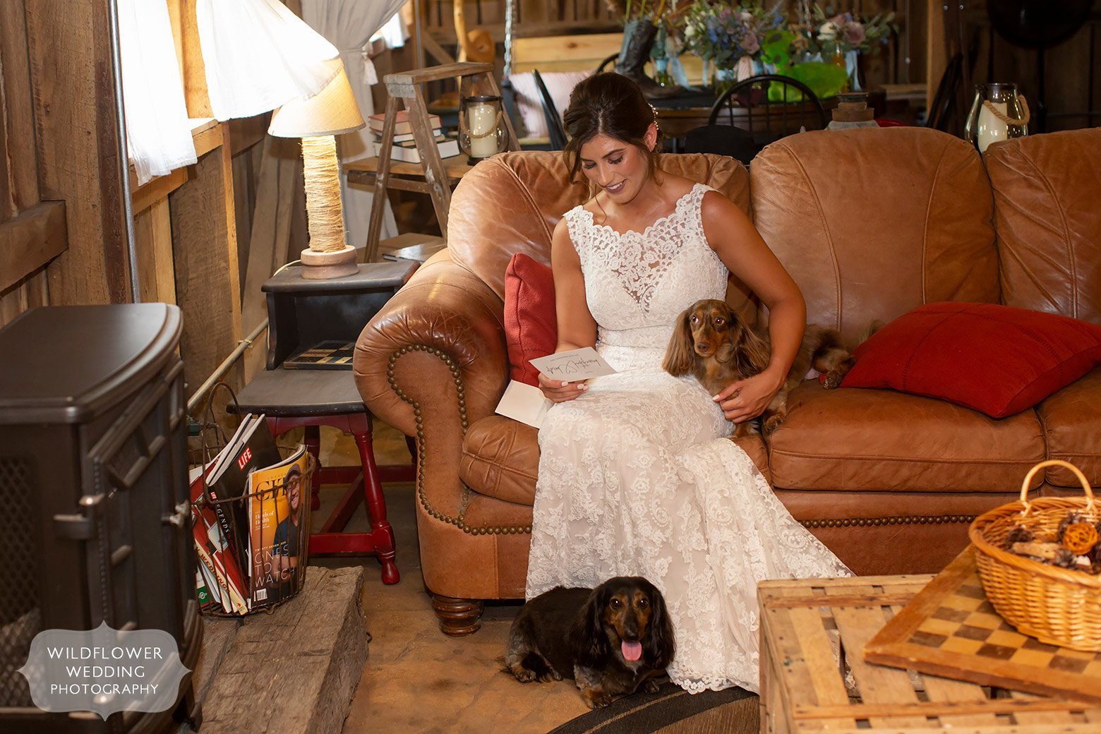 Bride on the couch with dogs while reading groom's letter.