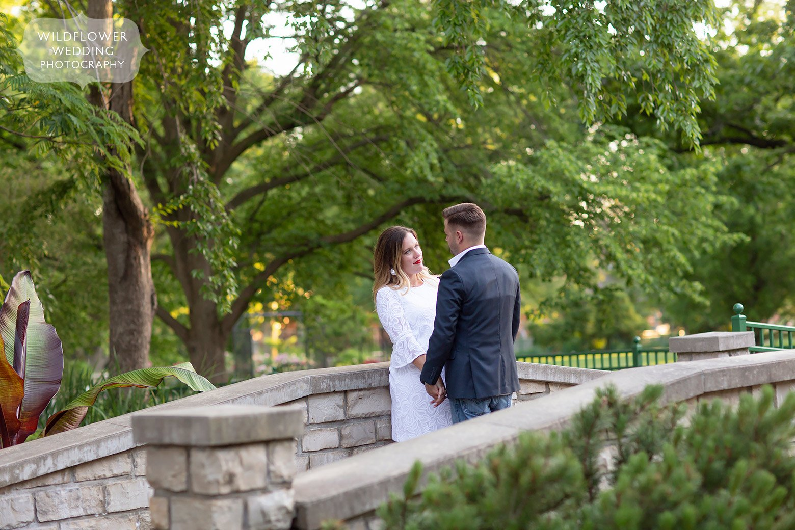 Couple stands on stone bridge at Shelter Gardens in Columbia, MO.