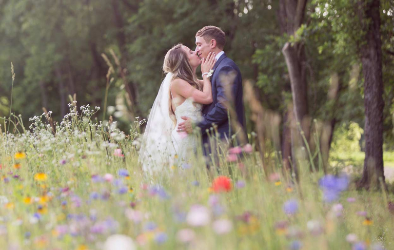 Bride and groom kissing in a field of wildflowers during summer wedding.