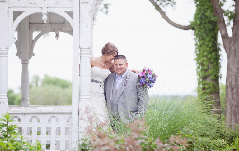A bride and groom share a moment on an old farmhouse front porch at the Blue Bell Farm in Fayette, MO.