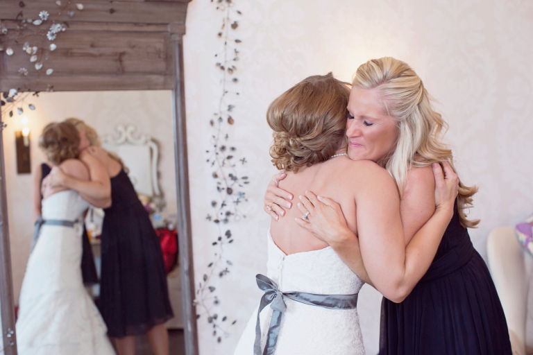 A bride hugs her maid of honor and best friend in the bridal suite at Blue Bell Farm.