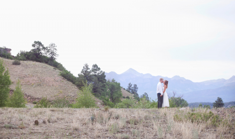 A bride and groom kiss at dusk during their Colorado destination wedding.