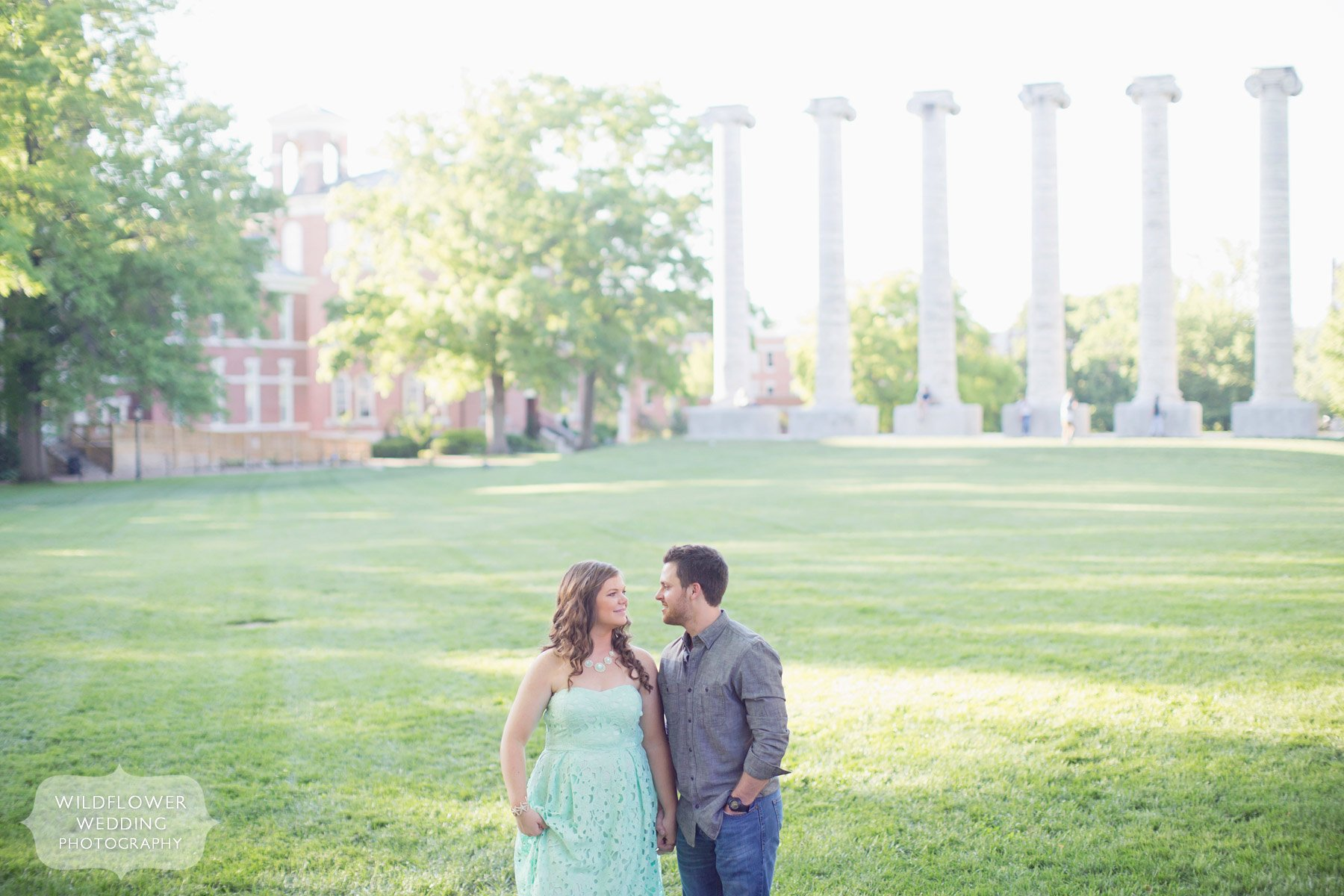 Photo of an engaged couple in front of the historic columns on the quadrangle of Mizzou campus in Columbia, MO.