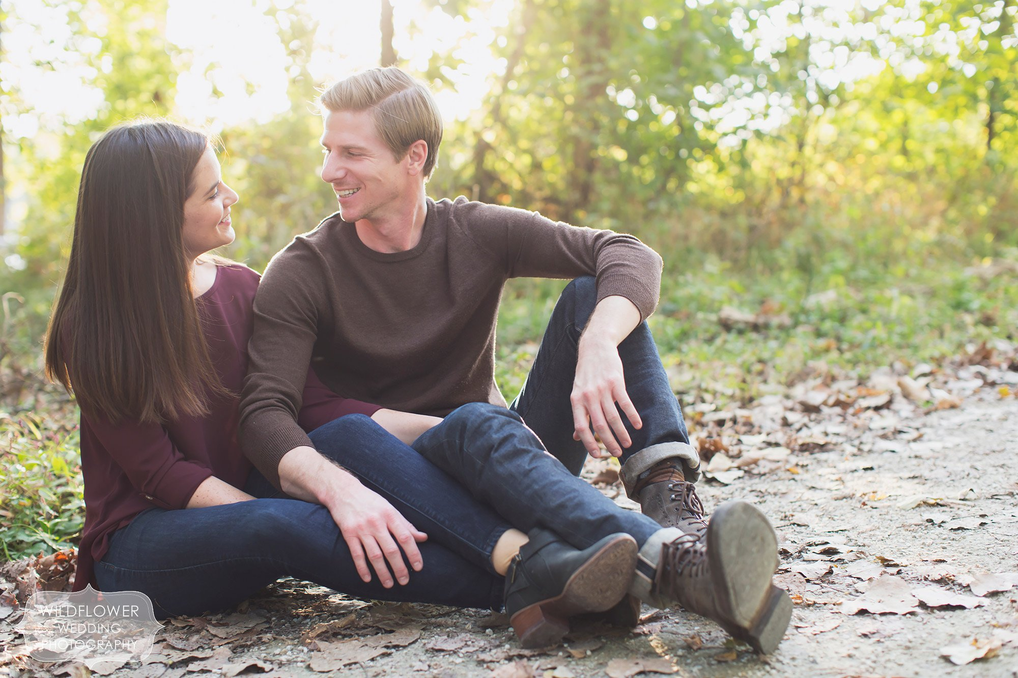 Couple sits on the ground along the Katy Trail near Cooper's Landing during their October engagement session.