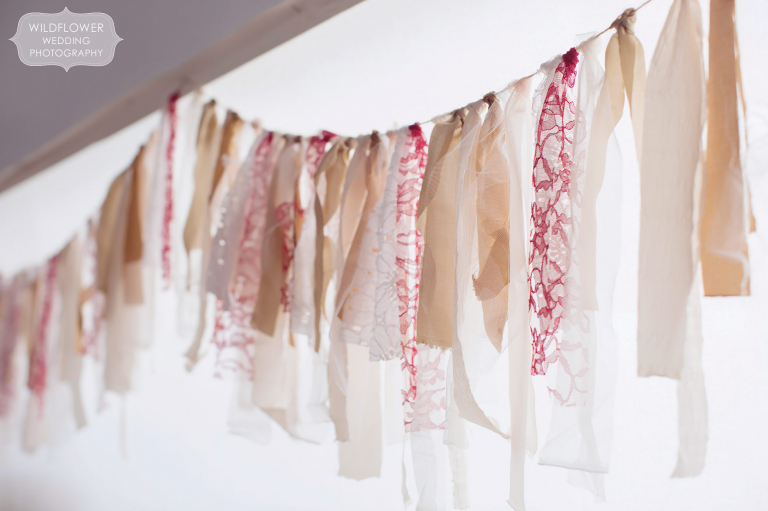A fabric scrap garland of beige, blush and white lace fabric was draped around the barn for this winter wedding in MO.