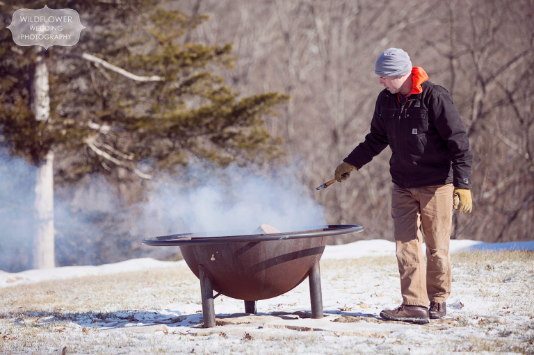 The owner of the property tends to the fire pit for this same-sex winter wedding in Columbia, MO.