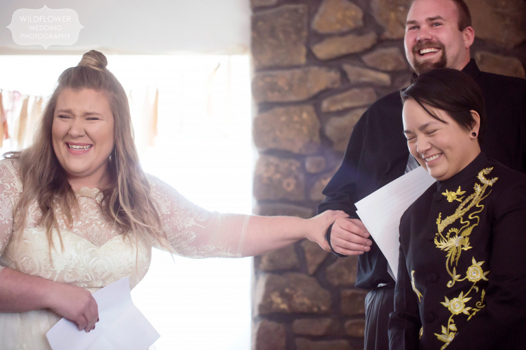 Great documentary photo of the bride crying and laughing while reading her vows to her partner during their gay wedding ceremony.