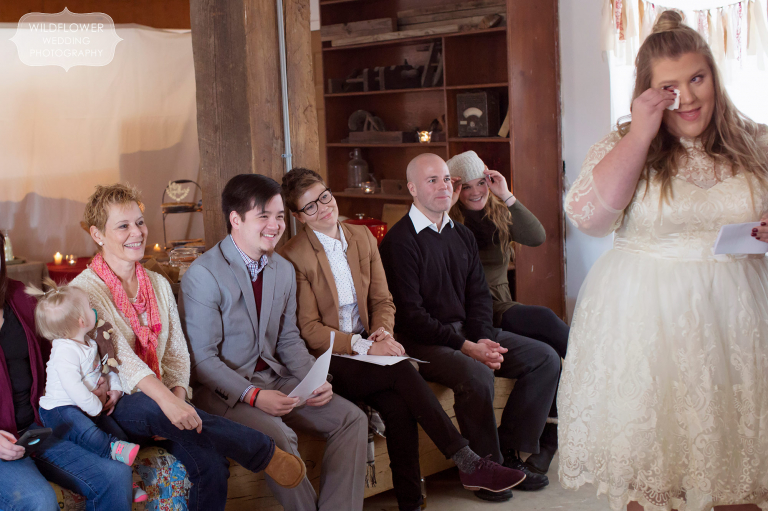 Candid moments of guests and family watching the winter wedding ceremony in the barn.