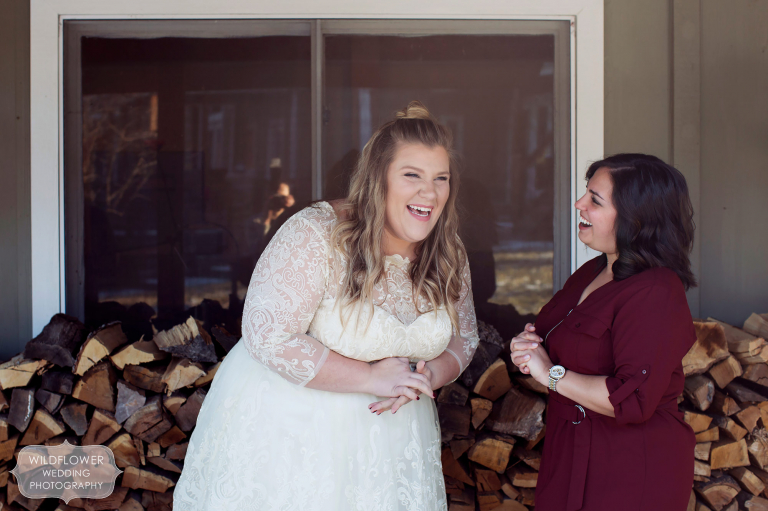Great documentary photo of the bride laughing with her best friend after her same sex ceremony in the winter.