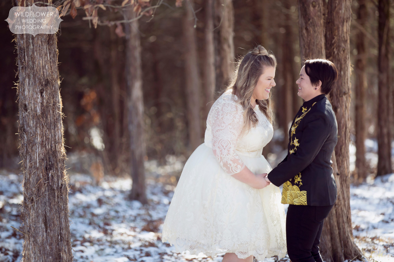 A couple laughs in the snowy woods before their Missouri same sex wedding ceremony.