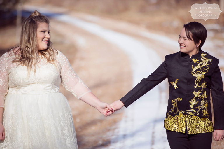 A queer couple poses on a snowy road before their same sex wedding ceremony in Columbia.