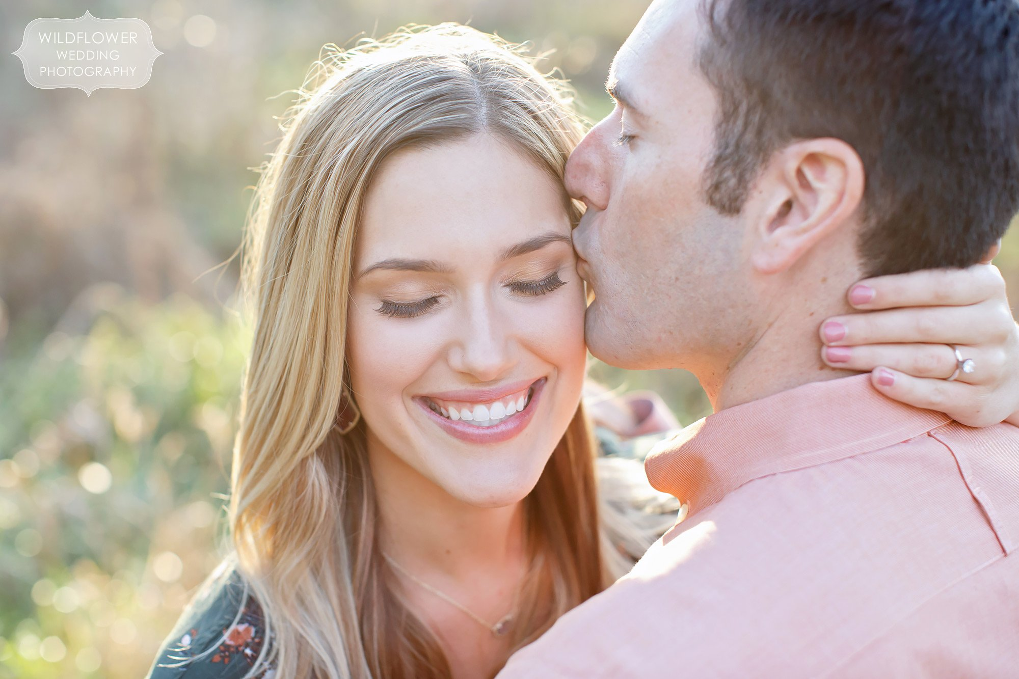 Anthropologie engagement photography pose with guy kissing girl on the cheek in sunbursty light at Grindstone Park.