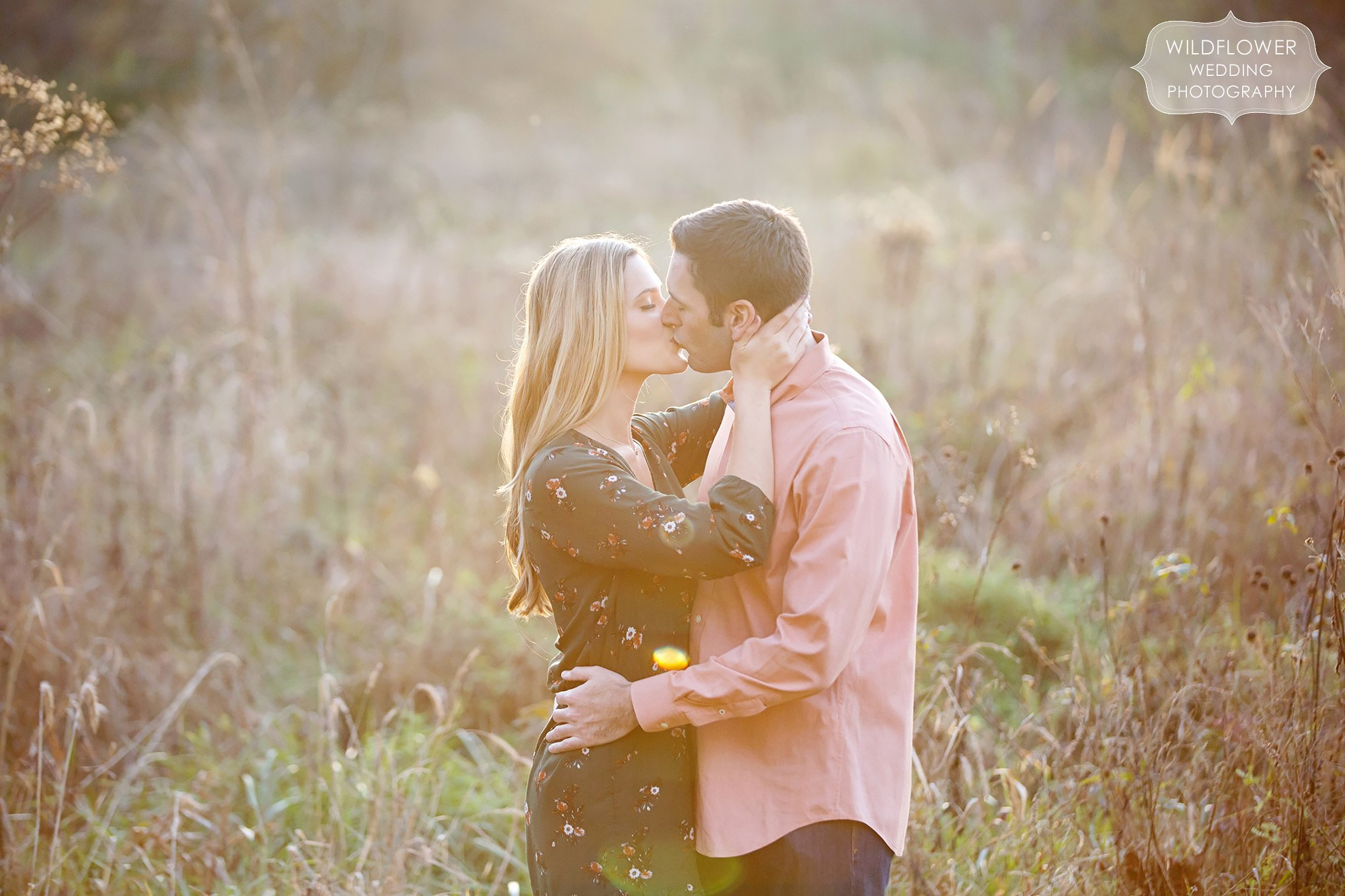 Sexy engagement photo of the couple kissing in a tall grass field at sunset in Columbia, MO.