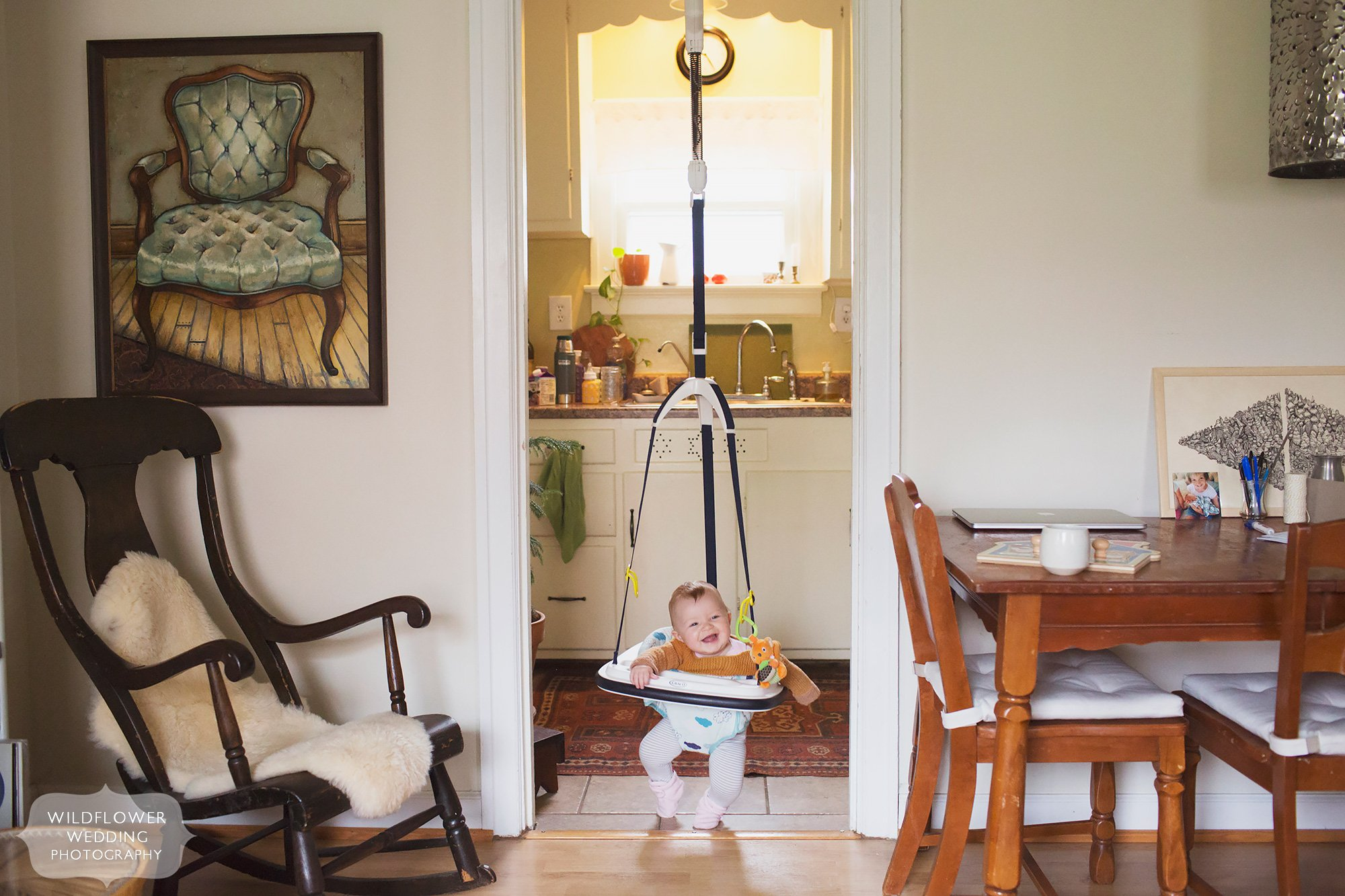 Artsy and documentary baby photography of eight month old in doorway bouncer at home in Columbia, MO.
