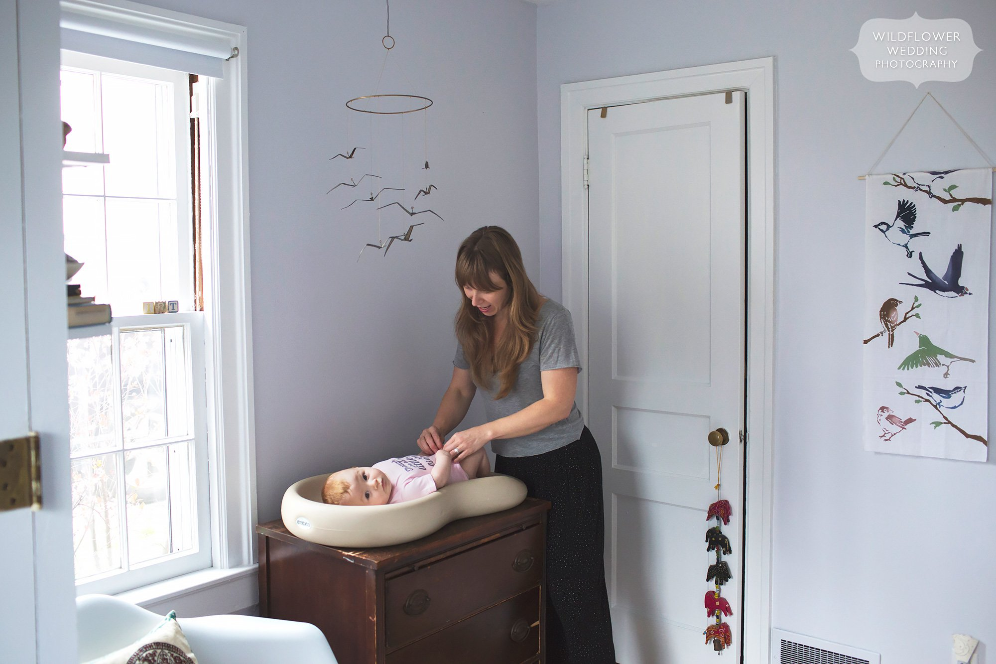 Candid photo of mother changing baby's diaper on Keekaroo Peanut at home during photo shoot in MO.