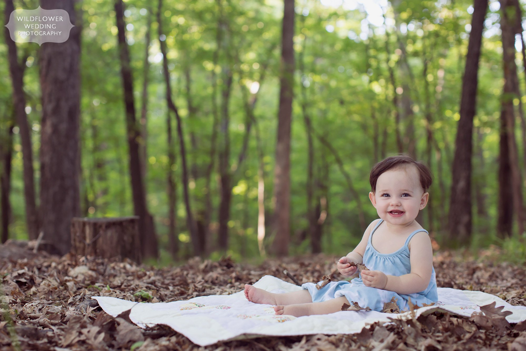 Baby sits on a picnic blanket in the middle of the woods during this family photo session in Columbia.