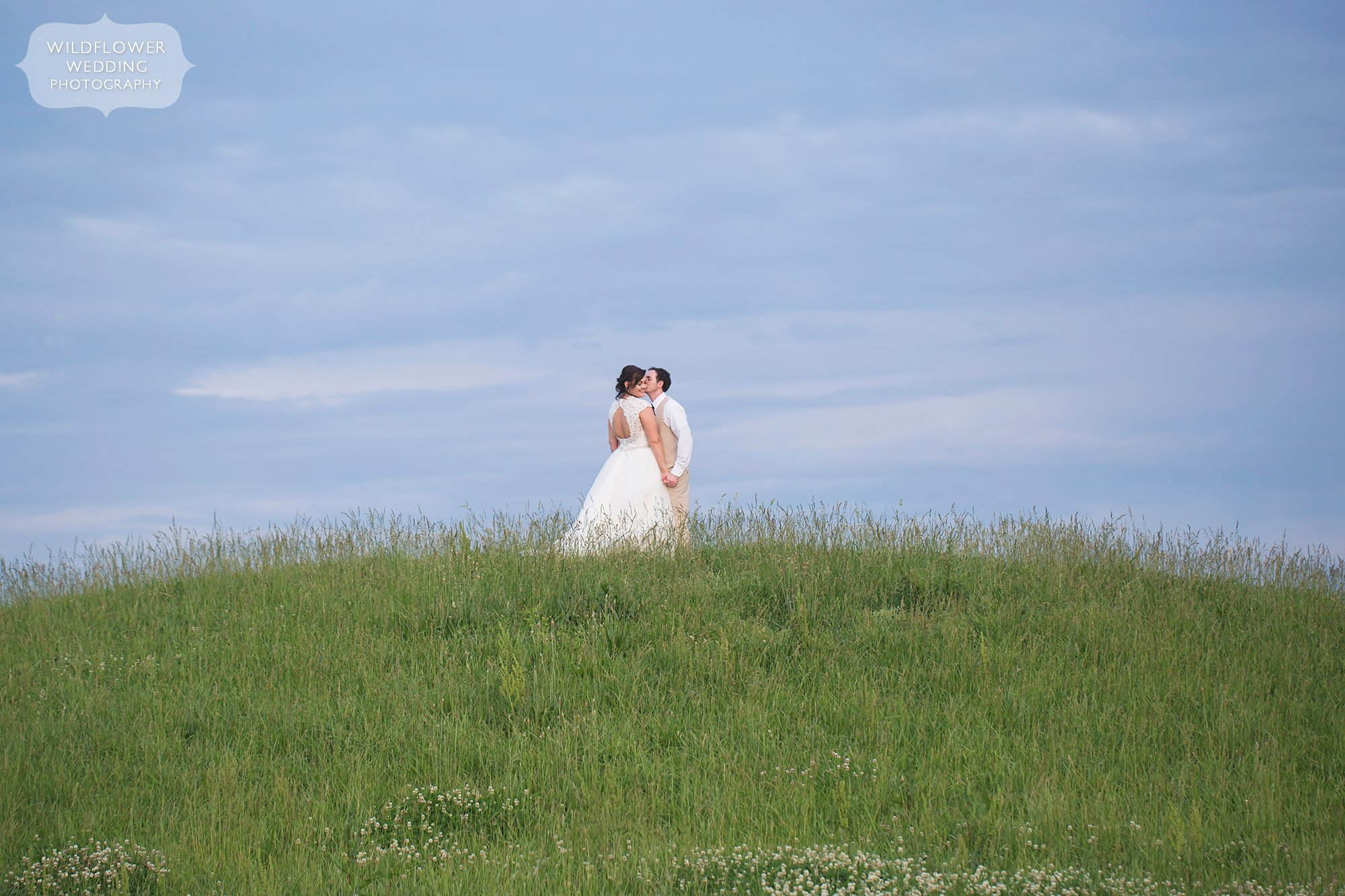 Bride and groom stand on a grassy hill for this artistic portrait at the MU Bradford Research Farm in Columbia, MO.