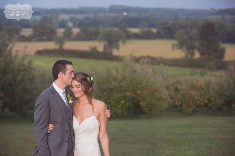 The groom kisses the bride's forehead during a romantic Missouri barn wedding at the Weston Red Barn Farm.