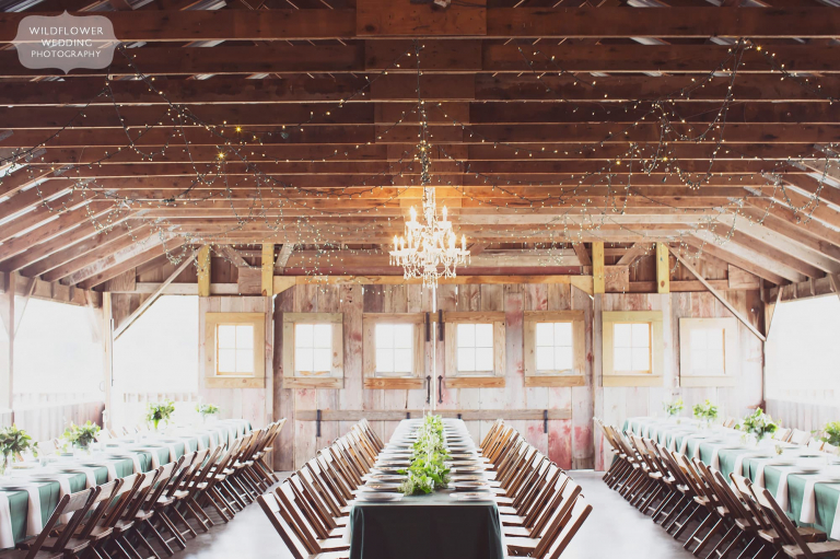 Long dinner tables are set with green tablecloths for this romantic Missouri barn wedding.