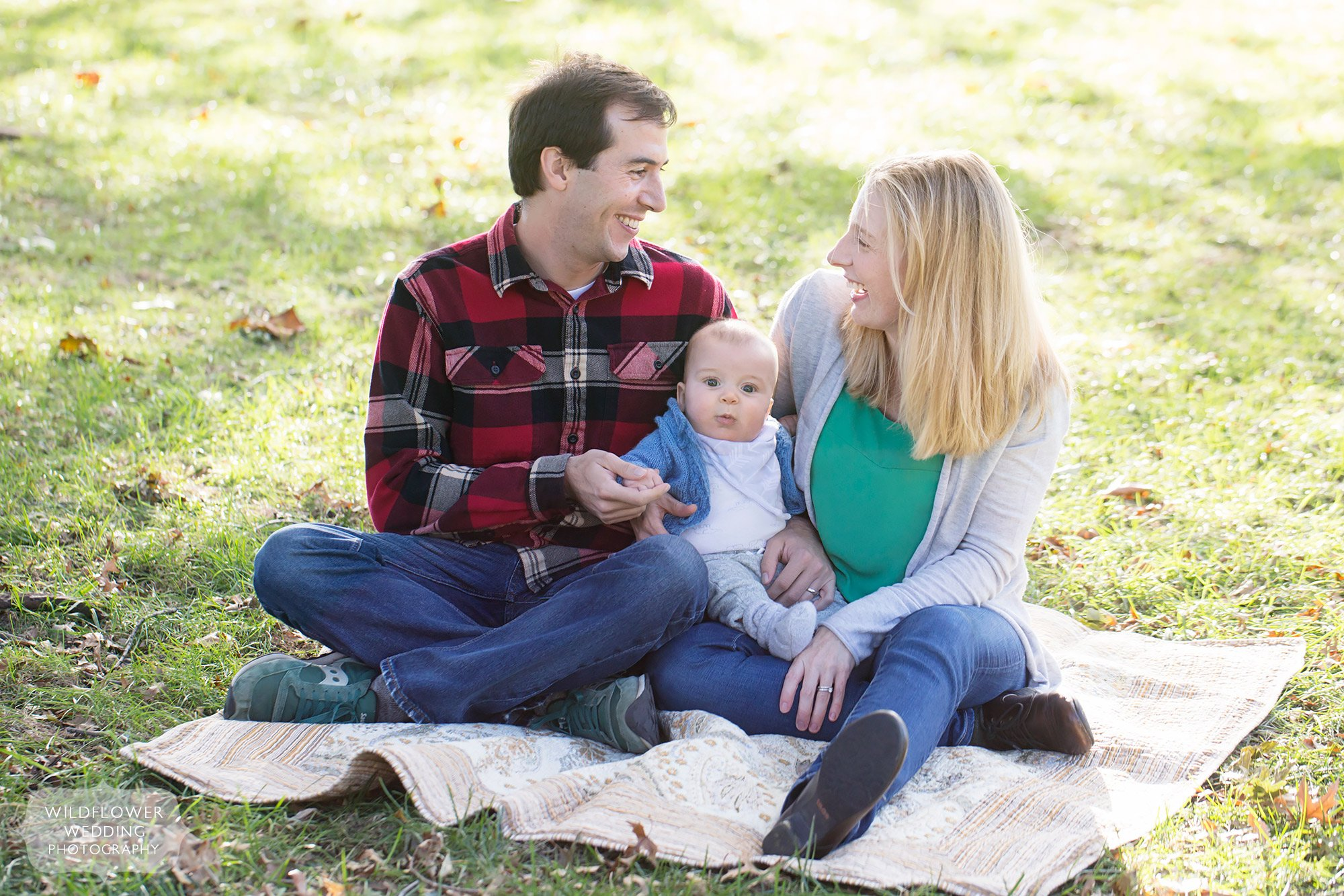 Parents and their baby sit on a quilt in Loose Park for a family photo session in the fall.