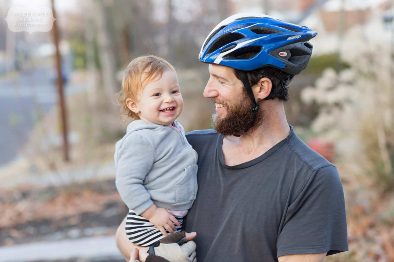 Dad wearing a bicycle helmet poses with his 18 month old toddler outside.