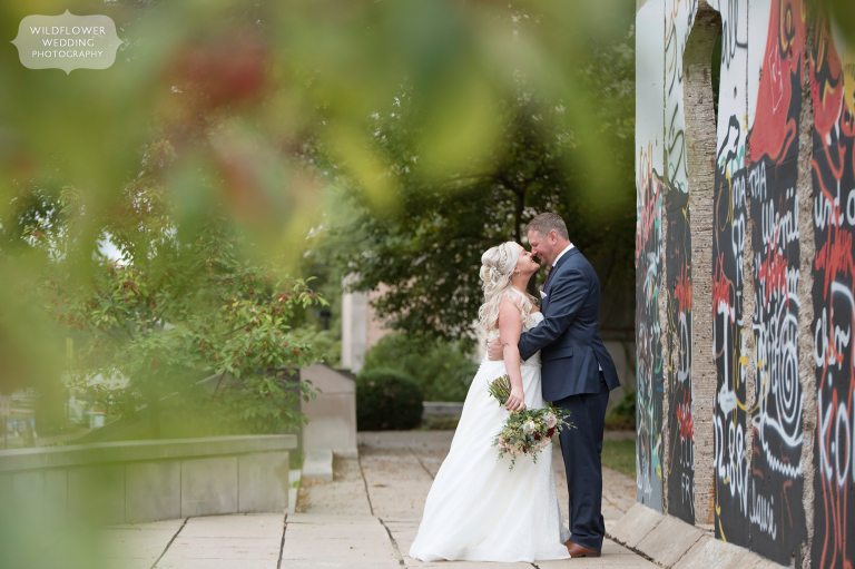 The bride and groom kiss outside before their Churchill Museum wedding by the Berlin Wall in Fulton, MO.