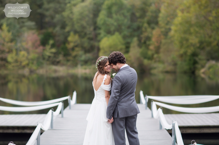 The bride and groom stand on the dock before their Little Piney Lodge wedding.