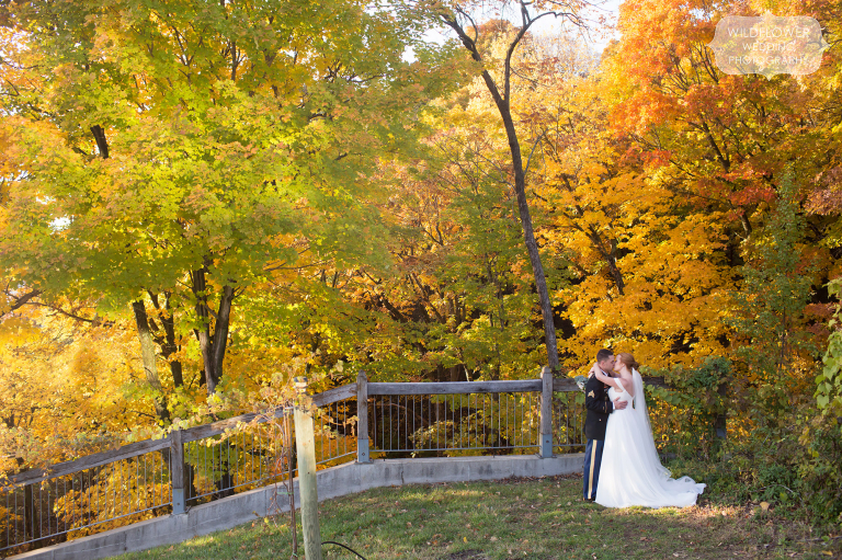 Bride and groom kiss on the blufftop at Les Bourgeois October wedding.