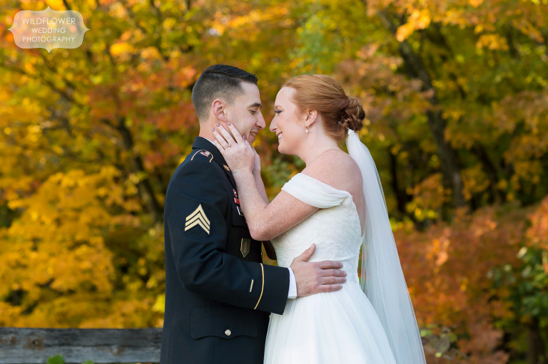 Bride and groom in the woods at their Les Bourgeois October wedding with fall colors.