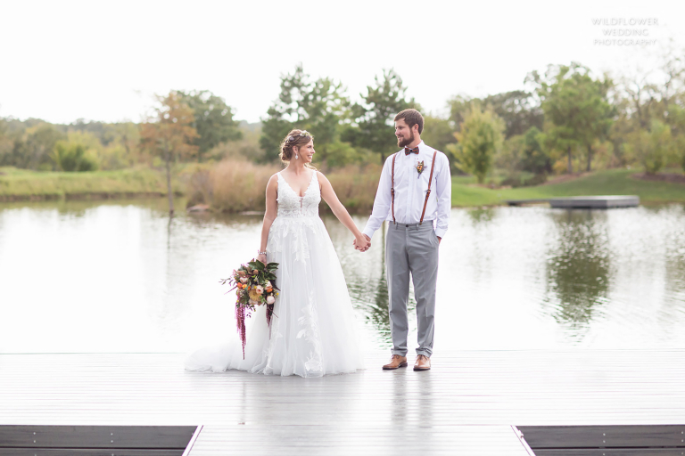 Bride and groom stand on edge of dock at October Hermann wedding in MO.