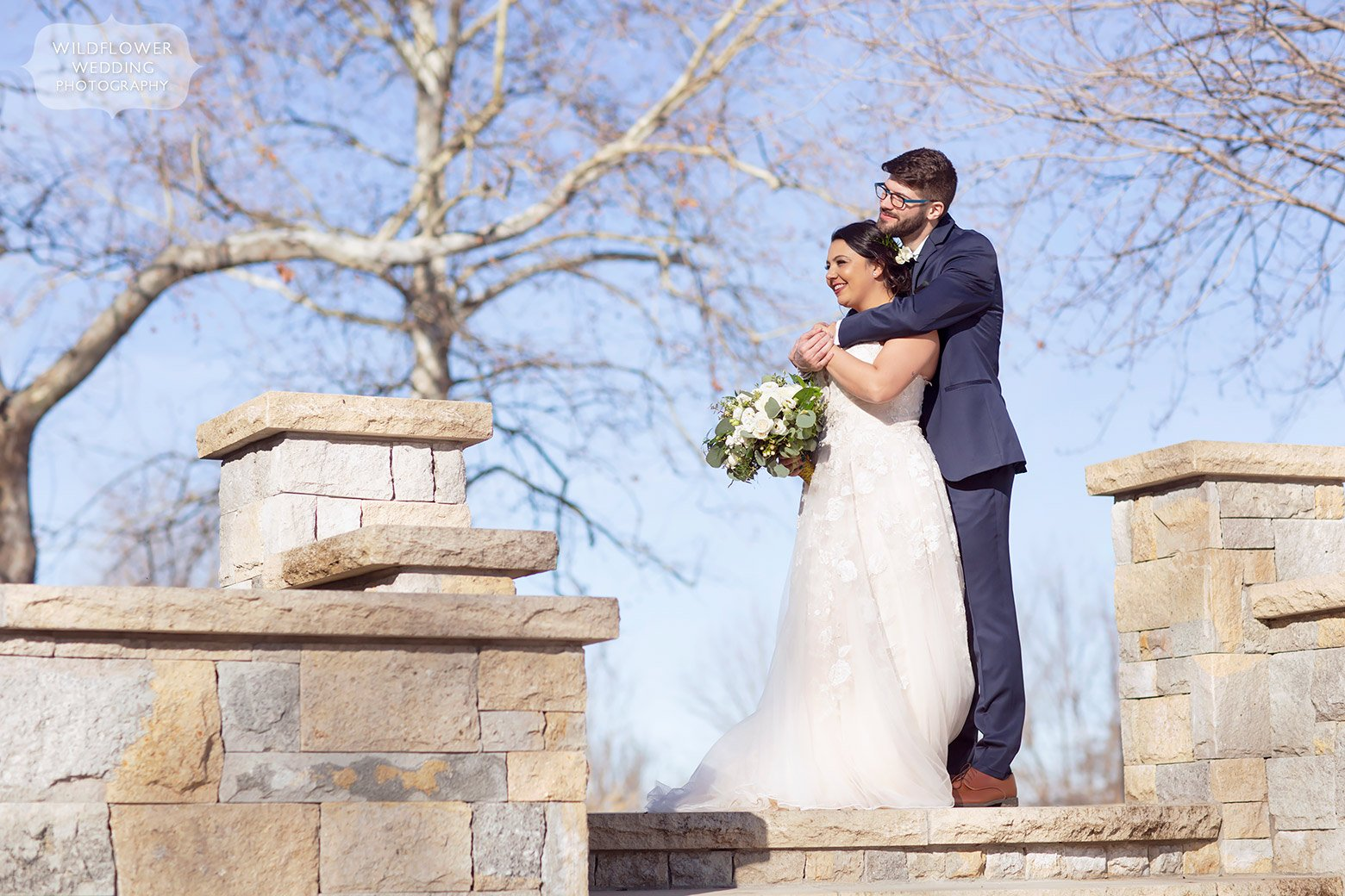 Bride and groom stand on patio at the Brownstone wedding venue in Topeka, KS.