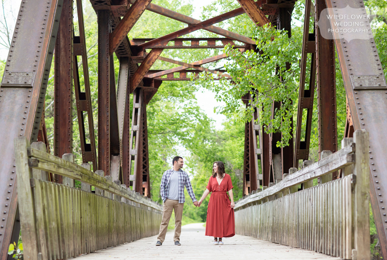 Couple stands on bridge during this Columbia, MO river engagement photo session.