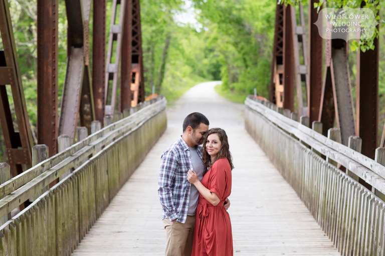 Couple stands on a rustic bridge