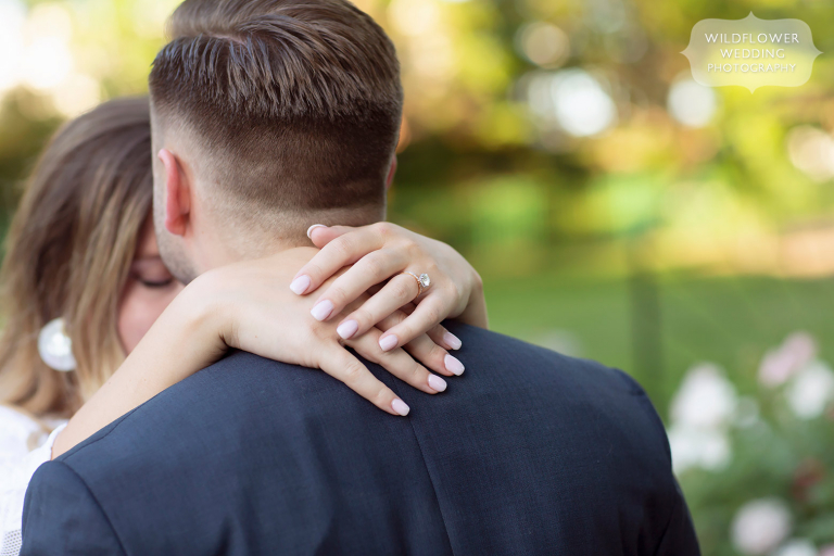 Girl wraps her arms around her fiance during Shelter Garden engagement session.