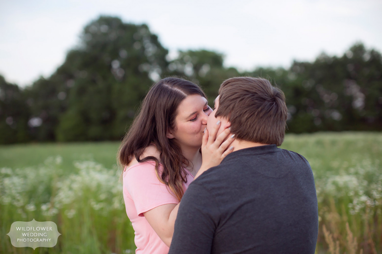 Girl pulls in boy for a kiss during Emerson Fields engagement photography session in mid-MO.