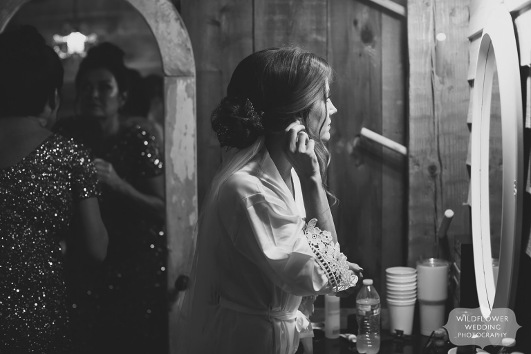 Bride looks in a mirror to fix her earring at the Weathered Wisdom Barn.